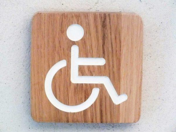 panneau avec pictogramme handicapé pour les toilettes